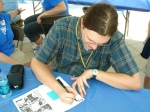 Andy Runton autographs a free comic he gave to the crowd.  We hope to get the Owly series in our media center.