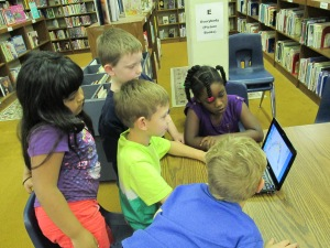 Students gathered around the netbook to plan out what they would share on the screencast.