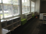 Straight shelves under windows will hold Nonfiction. Soft seating breaks up the shelving and provides a great window seat.