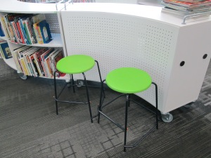 Some shelves have stools within the curves where students can sit and read or use the shelf as a counter/work space